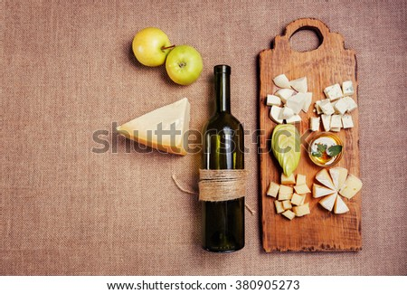 Cheese platter garnished with honey, apple and bottle of wine on rustic wooden board - stock photo