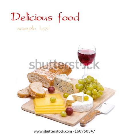 Cheese platter, grapes, ciabatta and a glass of red wine, isolated on white - stock photo
