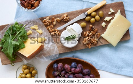 Cheese platter starter appetizer dinner snack, assortment of different cheeses, nuts, olives and grapes - stock photo