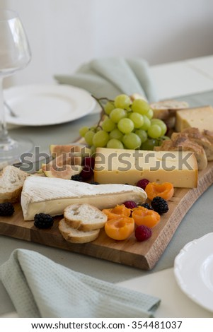 Cheese platter with French cheese and fruits - stock photo