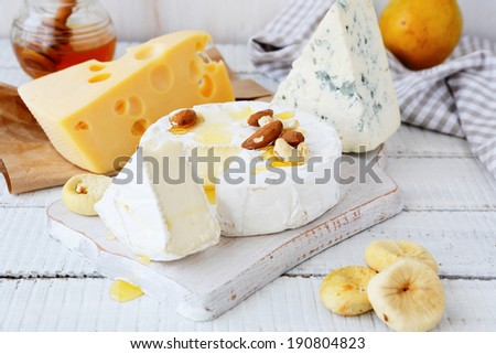 cheese platter with golden honey, food closeup - stock photo