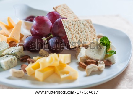 cheese platter with jam and grapes - stock photo