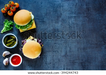 Cheese sandwiches with fresh vegetables on dark vintage background, border, top view, copy space. Vegetarian and healthy eating concept. - stock photo