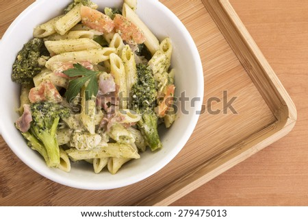 Cheese sauces and penne pasta with prosciutto and broccolis. - stock photo