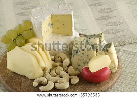 Cheese snacks and nuts on a wood platter. - stock photo