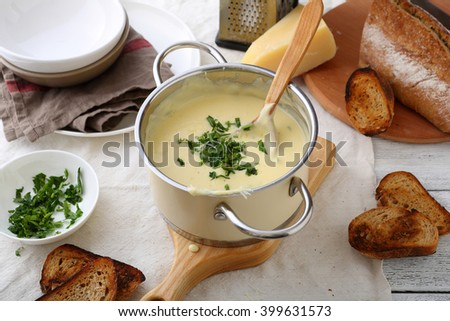 cheese soup in pan on table, fresh food cooking - stock photo