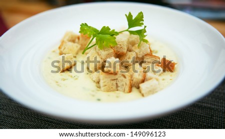 Cheese soup served with toasts - stock photo