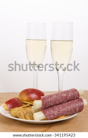 Cheese sticks wrapped in hard salami and served with white wine and apples with salty crackers.  Vertical format on white background with copy space. - stock photo