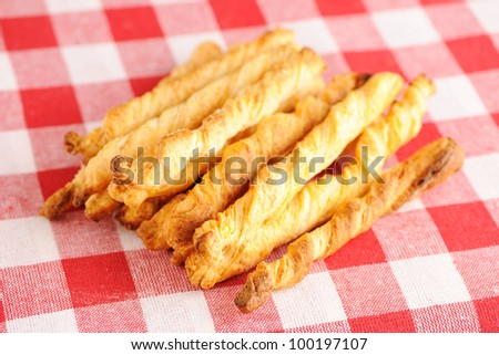 Cheese twists pastry over red cloth - stock photo