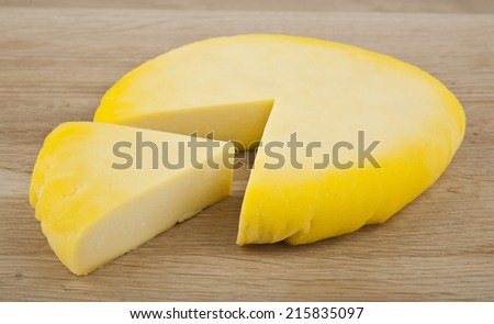 Cheese wheel on wooden table - stock photo