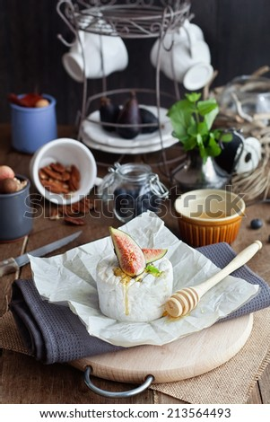Cheese with figs and honey on the wooden table with decoration on background - stock photo
