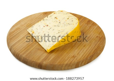 Cheese with herbs on a wooden plate - stock photo