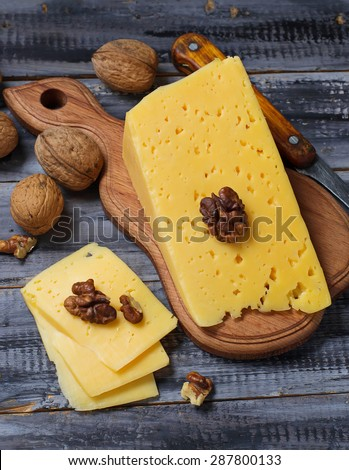 Cheese with nuts in wooden table. Selective focus - stock photo