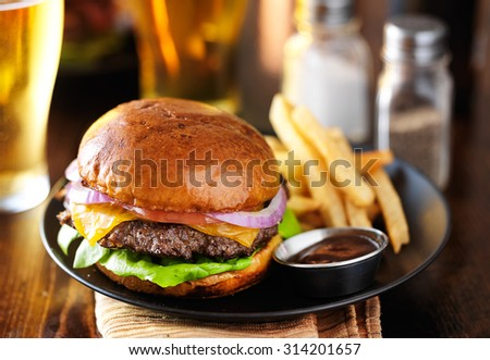 cheeseburger and fries on plate served with beer at restaurant - stock photo