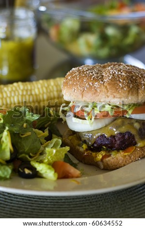 Cheeseburger on a Toasted Whole Wheat Bun Served Plated with Corn on the Cob and a Green Salad - stock photo