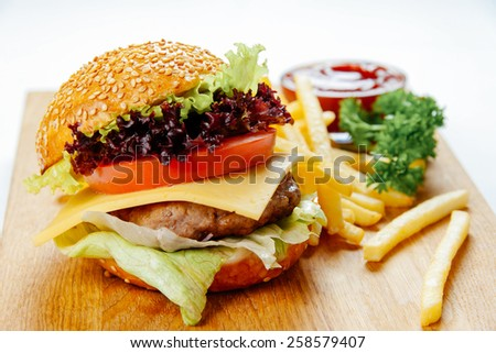 Cheeseburger with french fries on a wooden stand - stock photo