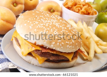 Cheeseburger with fries on the plate - stock photo