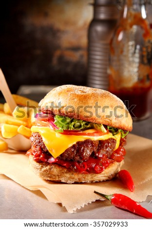 Cheeseburger with hot spicy chili pepper sauce and salad trimmings served with crispy potato chips on pieces of brown paper in a rustic restaurant - stock photo
