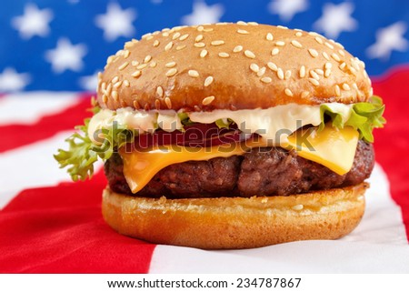 Cheeseburger with mayonnaise on USA flag - stock photo