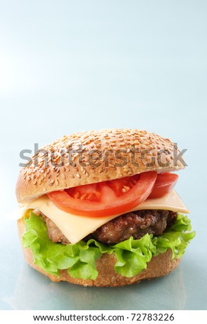 Cheeseburger with tomatoes and lettuce on grey background - stock photo