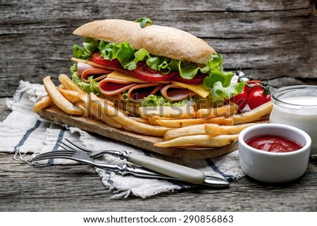 Cheeseburgers on sesame buns with succulent beef patties and fresh salad ingredients - stock photo