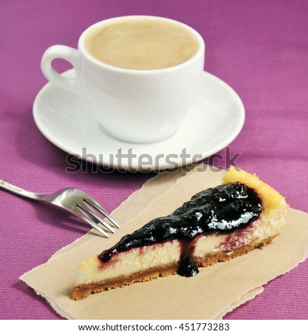Cheesecake slice and cup of coffee closeup on purple background. Breakfast concept - stock photo