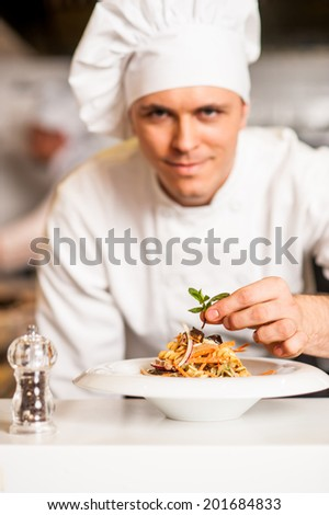Chef adding final touch to delicious salad - stock photo