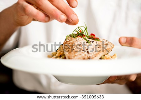 Chef adding final touch to tuna appetizer - stock photo