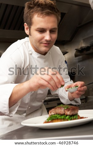 Chef Adding Seasoning To Dish In Restaurant Kitchen - stock photo