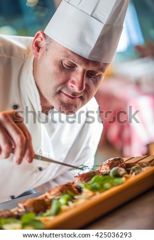 Chef. Chef cooking.Chef decorating dish. Chef preparing a meal. Chef in hotel or restaurant kitchen prepares decorating dish with tweezers. Chef cooking, only hands. - stock photo