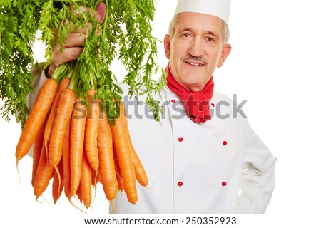 Chef cook holding up a fresh bunch of carrots - stock photo