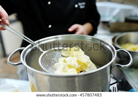 Chef cooking delicious french fries in a silver pot - stock photo