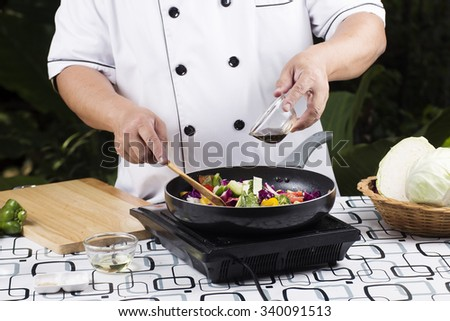 Chef cooking stir fried vegetable on the pan - stock photo