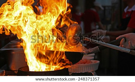 Chef Cooking With Fire In Frying Pan. Professional chef in a commercial kitchen cooking flambe style. Chef frying food in flaming pan on gas hob in commercial kitchen.  - stock photo