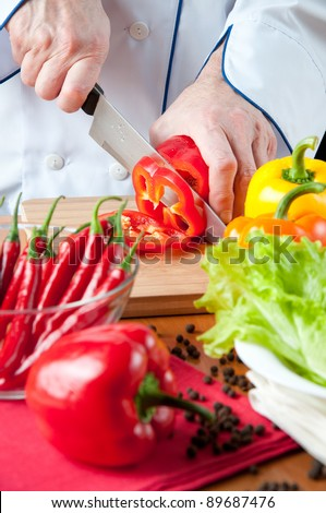 Chef cutting a red bell pepper - stock photo