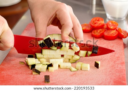 chef cutting eggplant little cubes over used red chopping board - stock photo