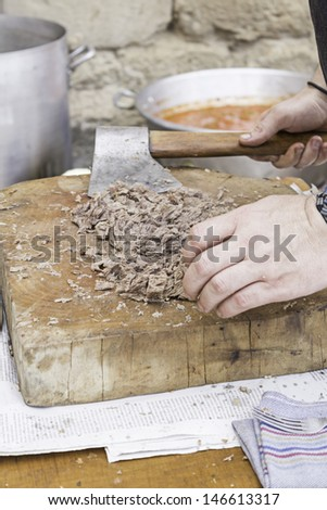 Chef cutting roast beef on wooden board, food and preparation - stock photo