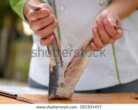 Chef cutting the herring for fillet with selective focus - stock photo