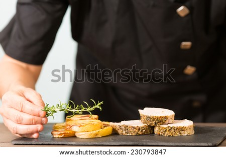 Chef decorating a pork tenderloin with potatoes - stock photo