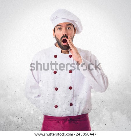 Chef doing surprise gesture over textured background - stock photo