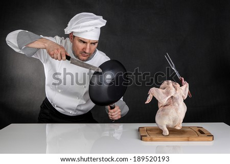 Chef fighting with knife and pan. Raw chicken attack - stock photo