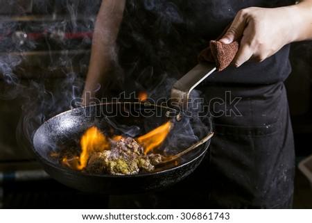 chef frying lamb on black pan - stock photo