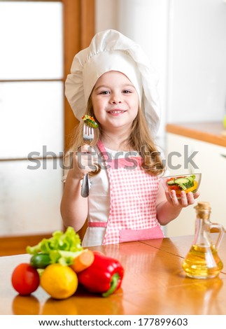 Chef girl preparing and tasting healthy food over white background - stock photo