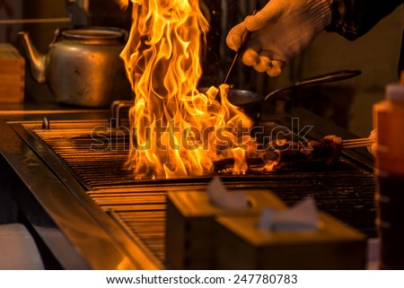 chef grilling bbq with flame of burning in restaurant. - stock photo