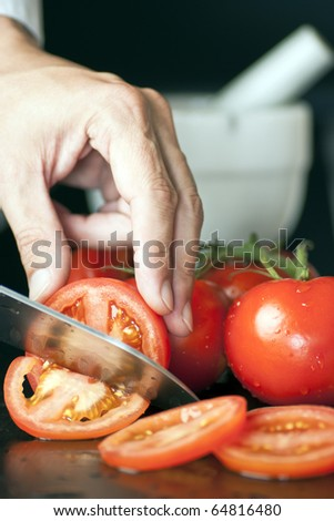 Chef Hand and Knife Slicing Tomato - stock photo