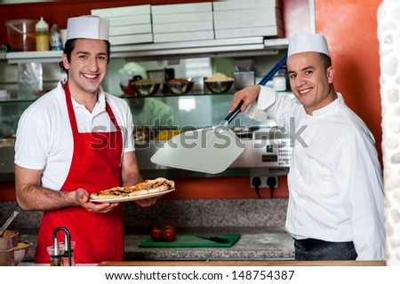 Chef handing over pizza to male assistant - stock photo