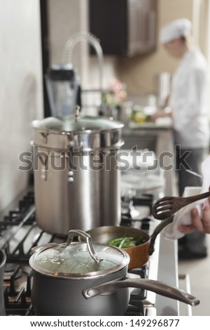 Chef heating saucepan on stove with coworker in background - stock photo