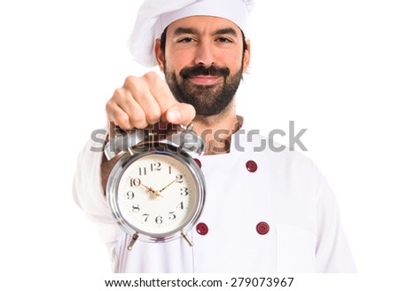 Chef holding a clock over white background - stock photo