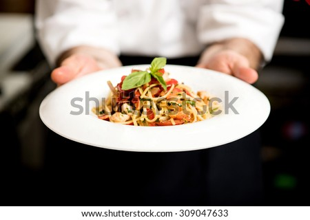 Chef holding hot spaghetti to serve in the restaurant - stock photo