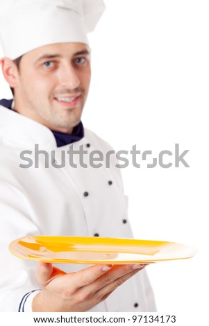 Chef holding plate with something. Focused on plate. Isolated over white. - stock photo